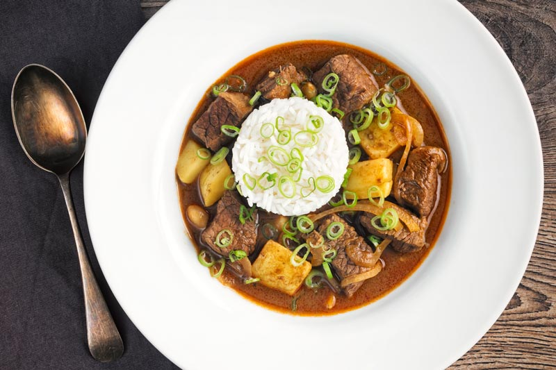 Overhead landscape image of a Thai beef massaman curry served with jasmine rice in a white bowl