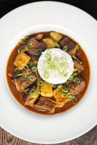 Overhead portrait image of a Thai beef massaman curry served with jasmine rice in a white bowl