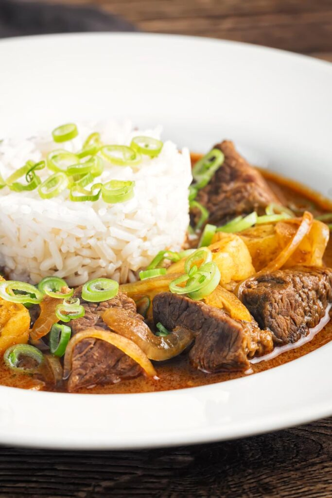 Portrait close up image of a Thai beef massaman curry served with jasmine rice in a white bowl