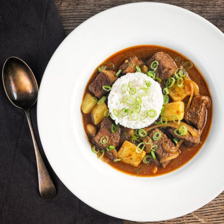 Overhead square image of a Thai beef massaman curry served with jasmine rice in a white bowl