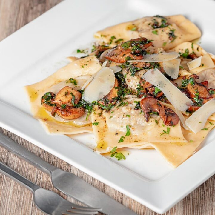 Square image of mushroom stuffed ravioli with balsamic mushrooms and Parmesan cheese shavings served on a white square plate