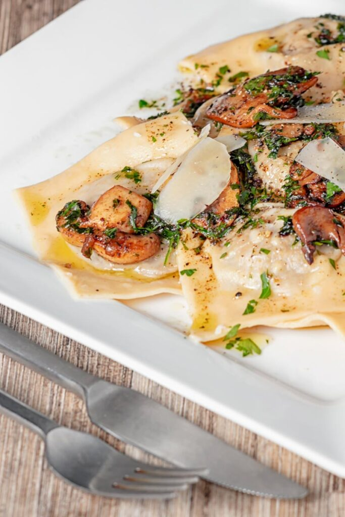 Portrait image of mushroom stuffed ravioli with balsamic mushrooms and Parmesan cheese shavings served on a white square plate