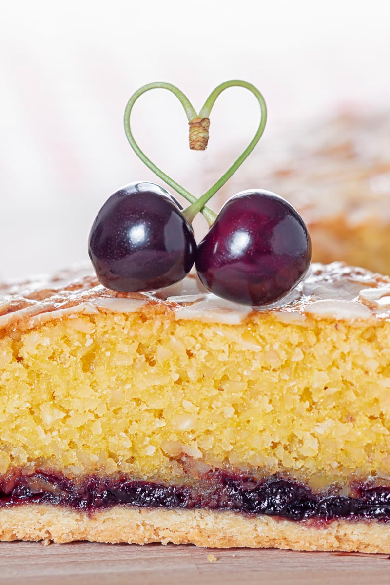 Portrait close up cross section of a Bakewell tart slice topped with a cherry heart
