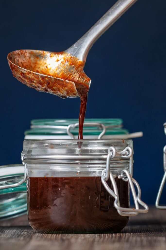 Square image of homemade Chinese plum sauce being decanted into storage jars