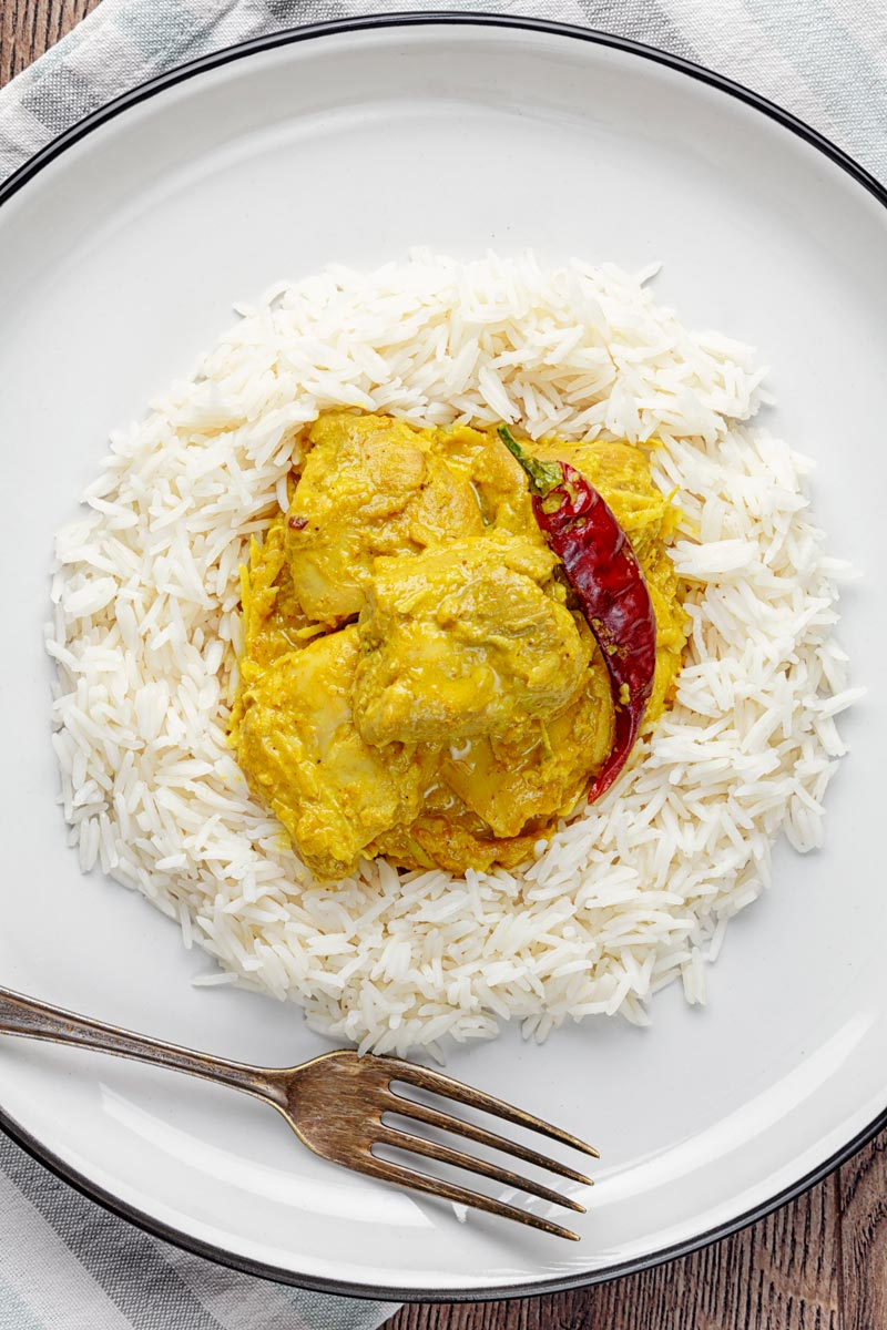 Portrait overhead image of a golden coloured coconut chicken curry served on a bed of Basmati rice with a chilli
