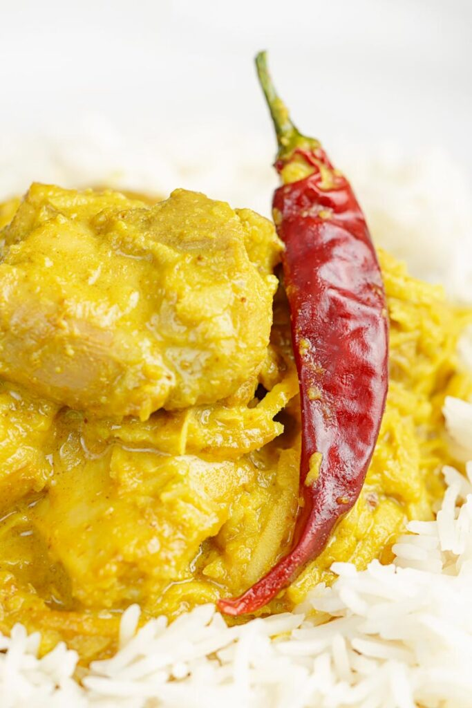 Portrait close up image of a golden coloured coconut chicken curry served on a bed of Basmati rice with a chilli