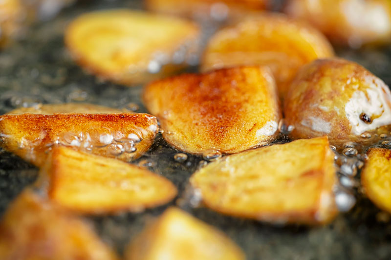 Landscape image of golden fried potatoes being shallow fried in oil