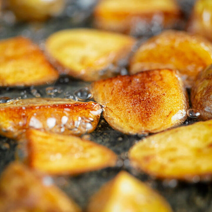 Square image of golden fried potatoes being shallow fried in oil