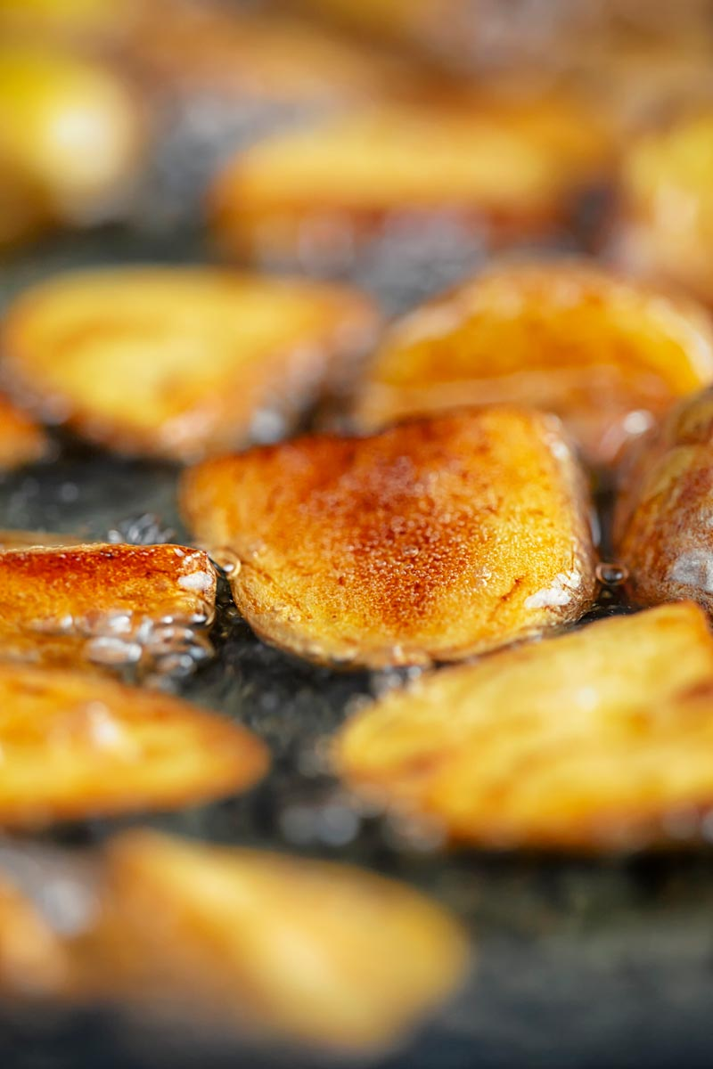 Portrait image of golden fried potatoes being shallow fried in oil