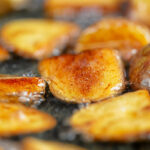Portrait image of golden fried potatoes being shallow fried in oil with text overlay