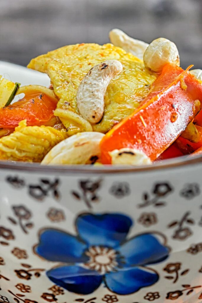 Portrait Close up image of chicken curry noodles served in an Asian style bowl decorated with a blue flower