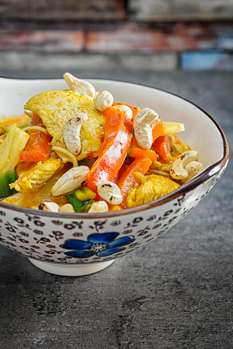 Portrait image of chicken curry noodles served in an Asian style bowl decorated with a blue flower