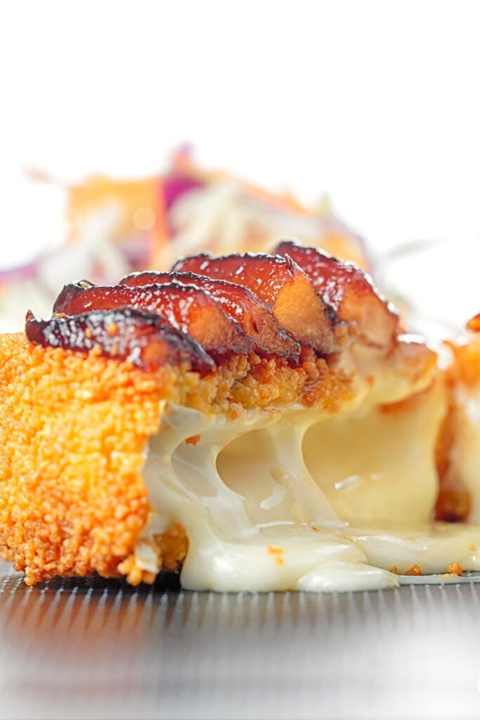 Portrait close up image of a fried Camembert Cheese with a balsamic pear topping cut open to show melted cheese filling