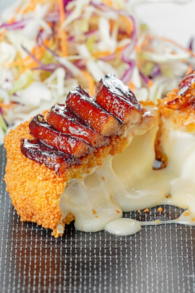 Portrait image of a fried Camembert Cheese with a balsamic pear topping cut open to show melted cheese filling