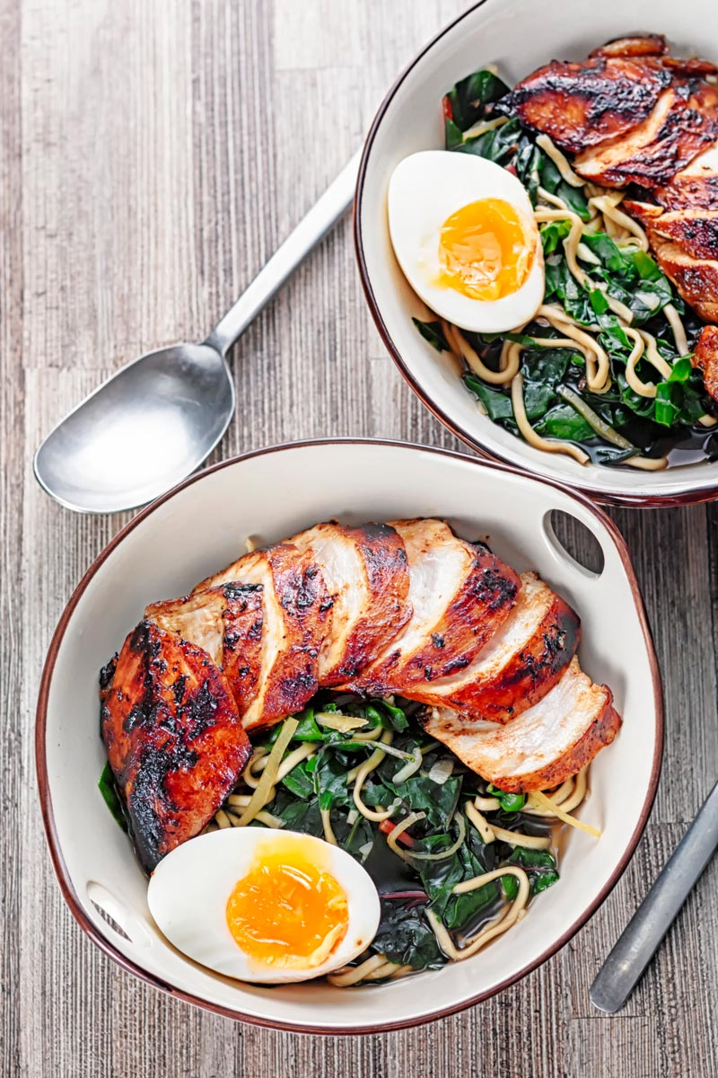 Portrait overhead image of a hoisin chicken ramen with a boiled egg and Swiss chard