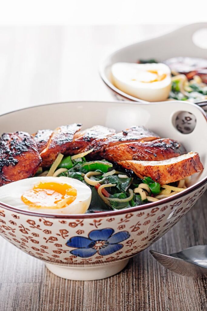 Square image of a hoisin chicken ramen with a boiled egg and Swiss chard served in an Asian style bowl decorated with a blue flower