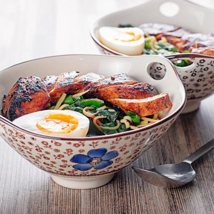Portrait image of a hoisin chicken ramen with a boiled egg and Swiss chard served in an Asian style bowl decorated with a blue flower