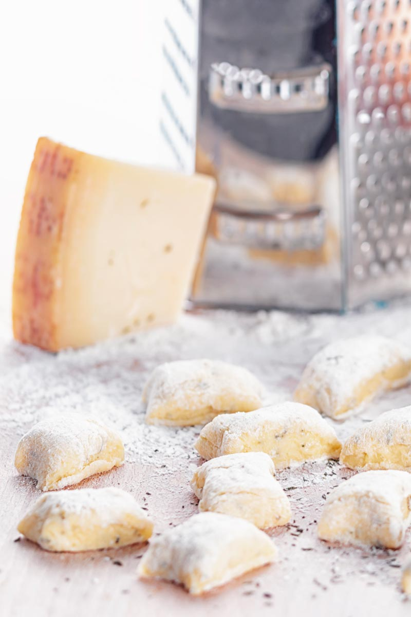 Portrait image of homemade potato gnocchi served on a board with a grater, eggs and Parmesan cheese