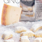 Portrait close up image of homemade potato gnocchi served on a board with a grater, eggs and Parmesan cheese with text overlay