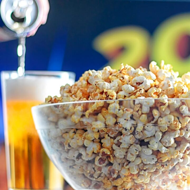 Square image of spiced popcorn in a glass bowl with a beer being poured in the background