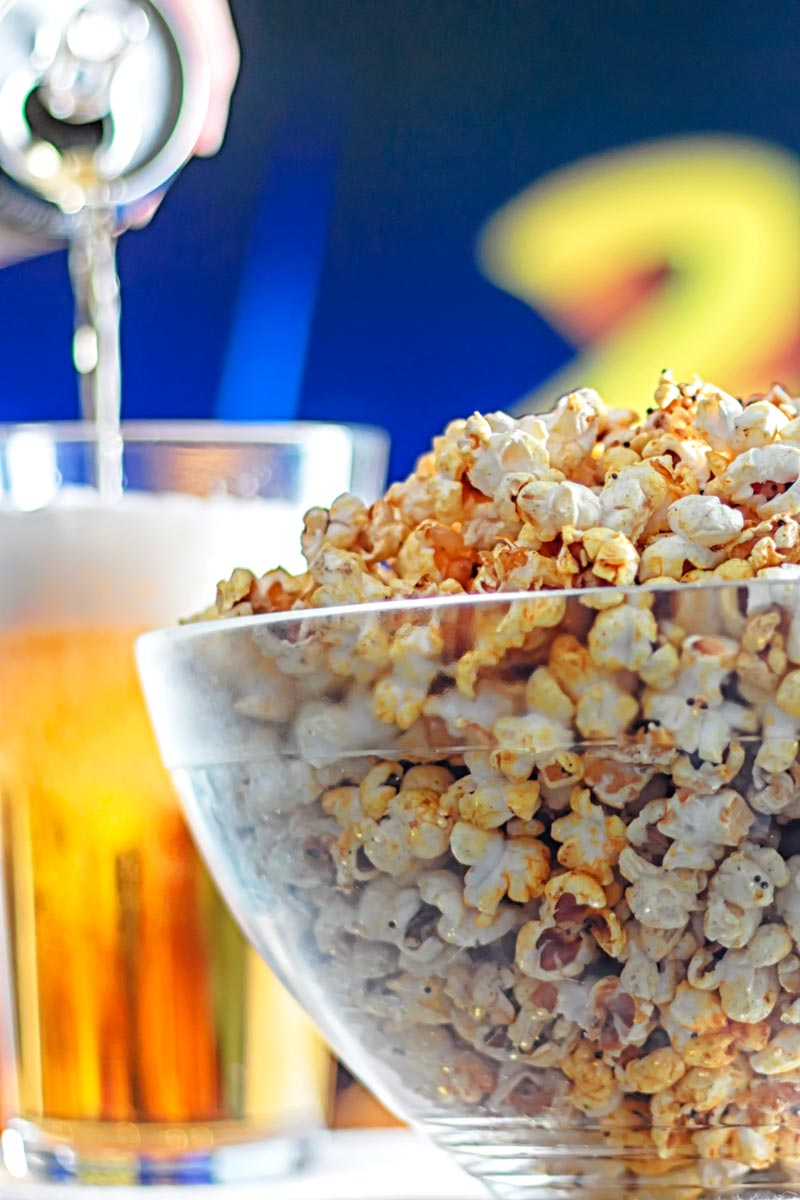 Portrait image of spiced popcorn in a glass bowl with a beer being poured in the background