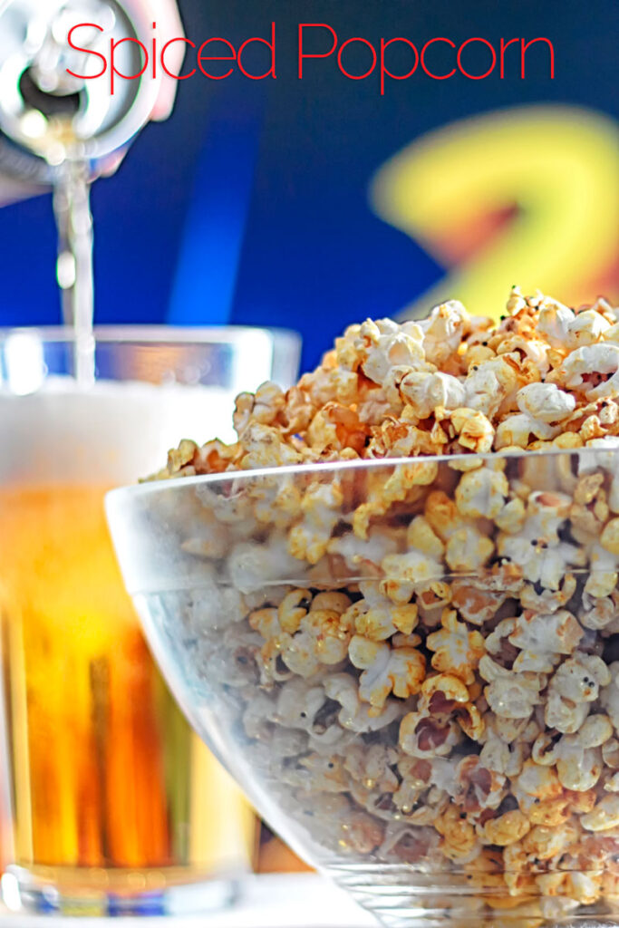 Portrait image of spiced popcorn in a glass bowl with a beer being poured in the background with text overlay
