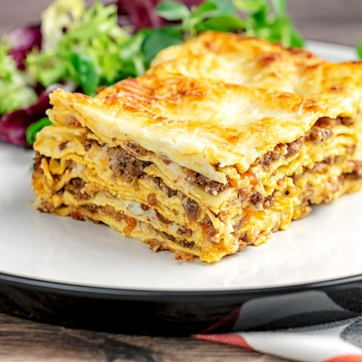 Square image of a classic Lasagna bolognese served as a slice on a plate showing layers