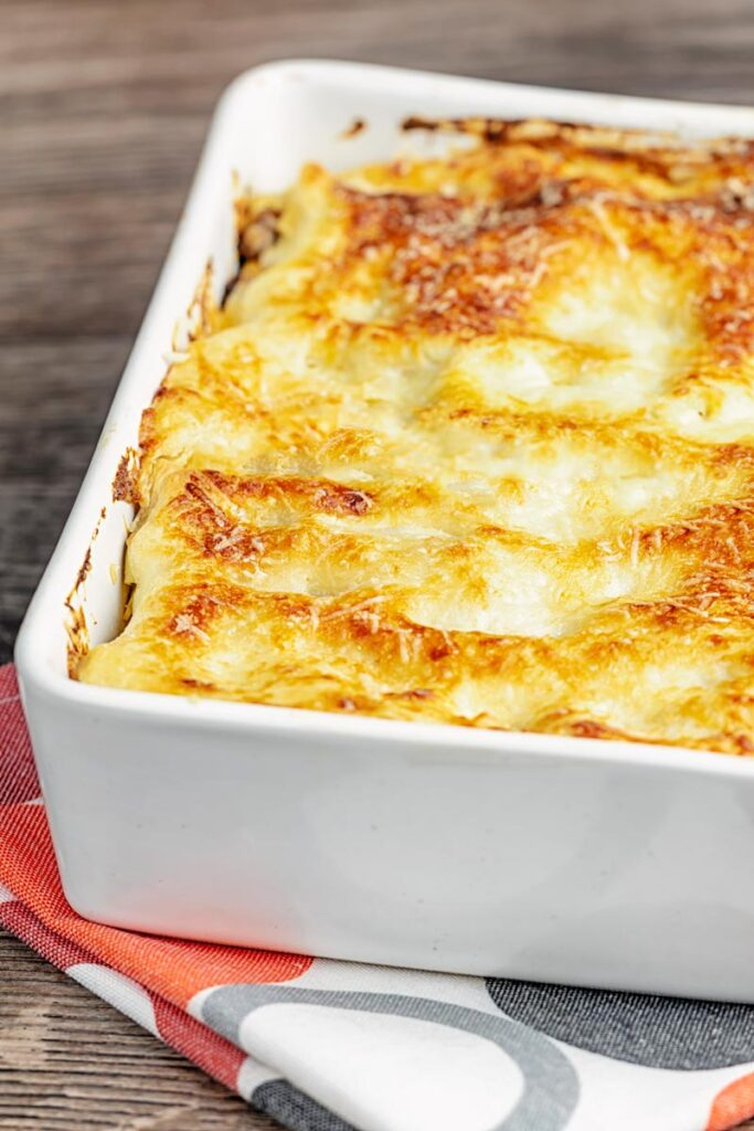 Portrait image of a classic Lasagna Bolognese in an oven proof white baking dish