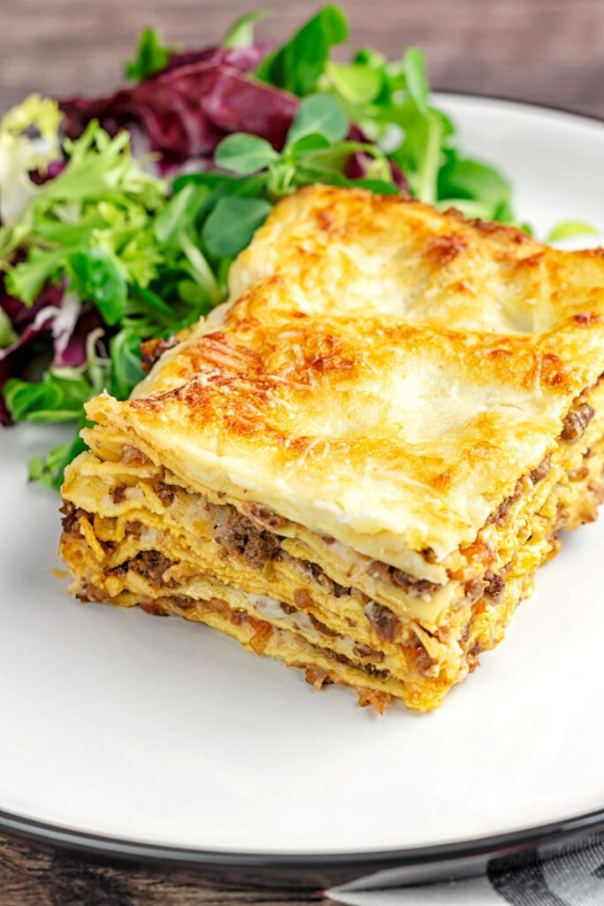 Portrait image of a classic Lasagna Bolognese served as a slice on a plate with side salad