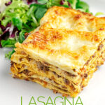 Portrait image of a classic Lasagna Bolognese served as a slice on a plate with side salad and text overlay