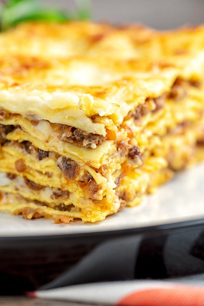 Portrait close up image of a classic Lasagna Bolognese served as a slice on a plate showing layering
