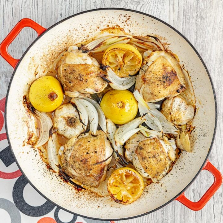 Square overhead image of chicken thighs cooked with onion lemon and garlic in an enamel cast iron pot