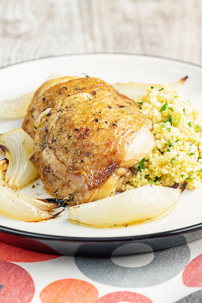 Portrait close up image of lemon and garlic chicken thighs served with roasted onions and a millet side dish served on a white plate