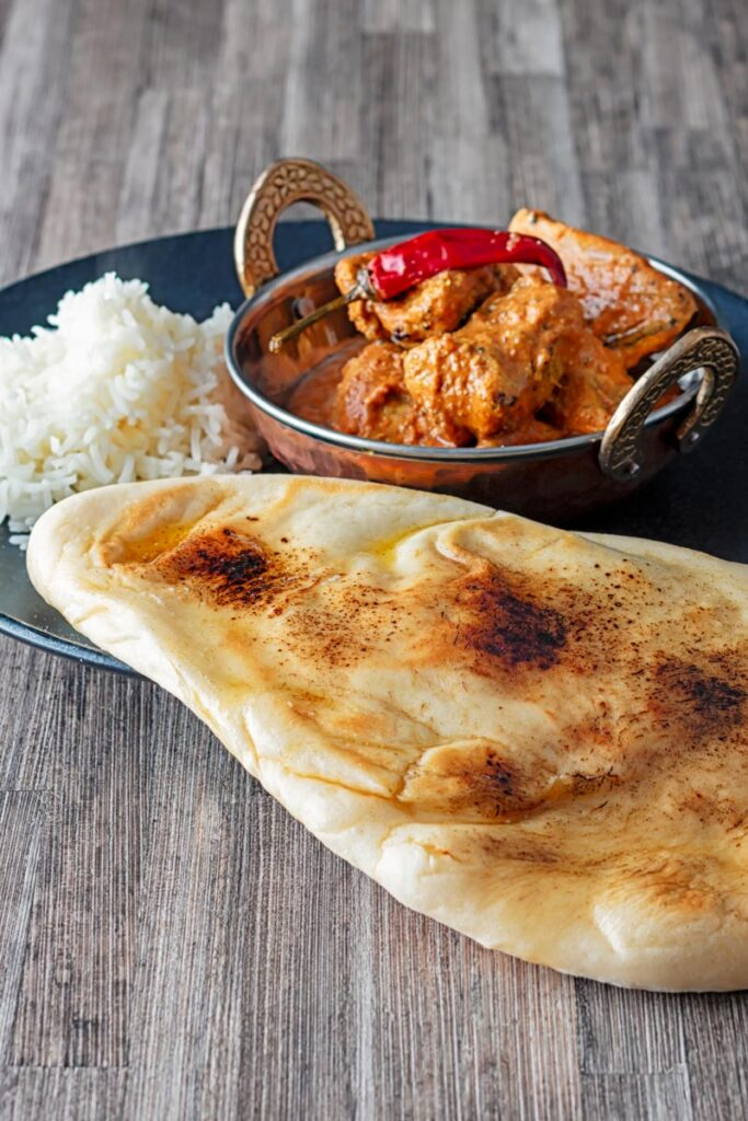 Portrait image of homemade naan bread served with a curry and rice