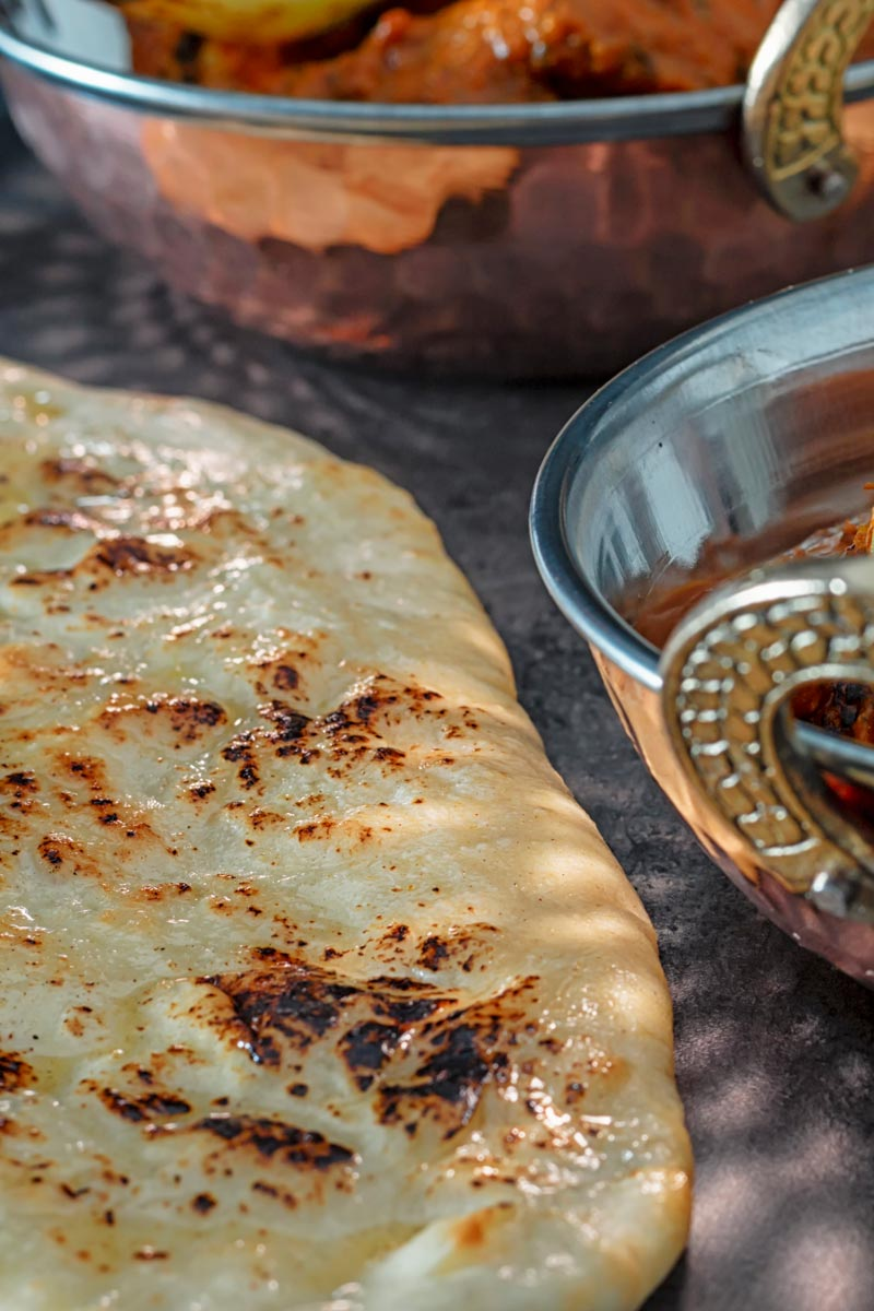 Portrait close up image of homemade naan bread glazed with ghee along side to copper plated curry dishes