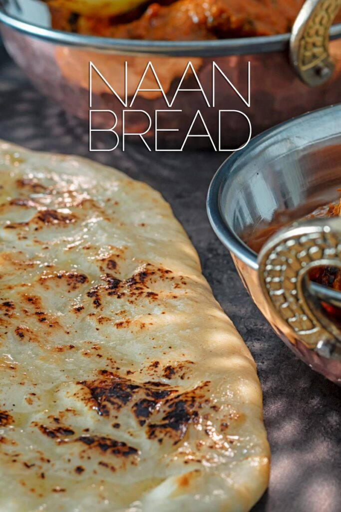 Portrait close up image of homemade naan bread glazed with ghee along side to copper plated curry dishes with text overlay
