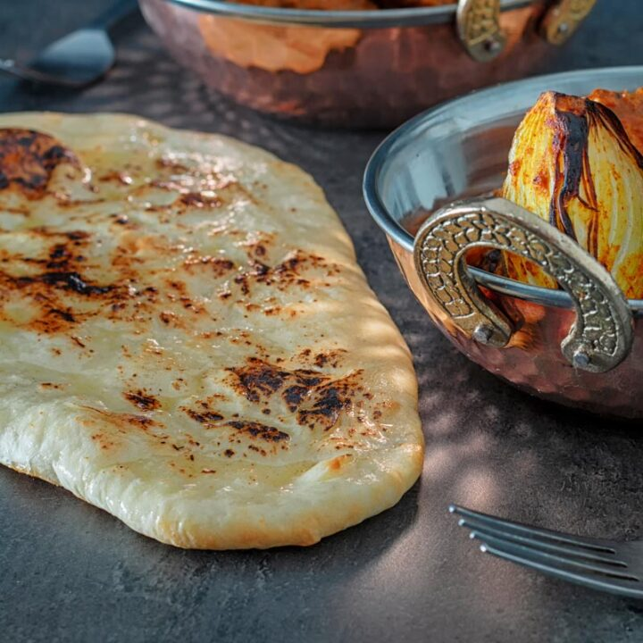 Square image of homemade naan bread glazed with ghee served with chicken tikka masala