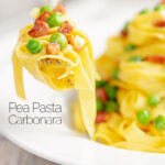 Portrait close up image of pasta carbonara with peas with a mouthful on a fork and the dish out of focus with text
