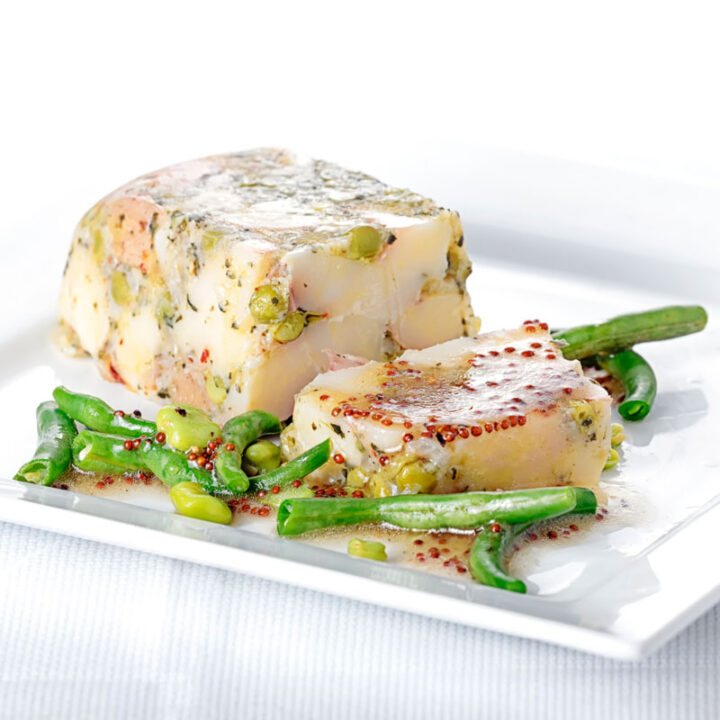 Square image of a vegetable terrine featuring peas and potatoes served on a white plate with beans and a mustard dressing