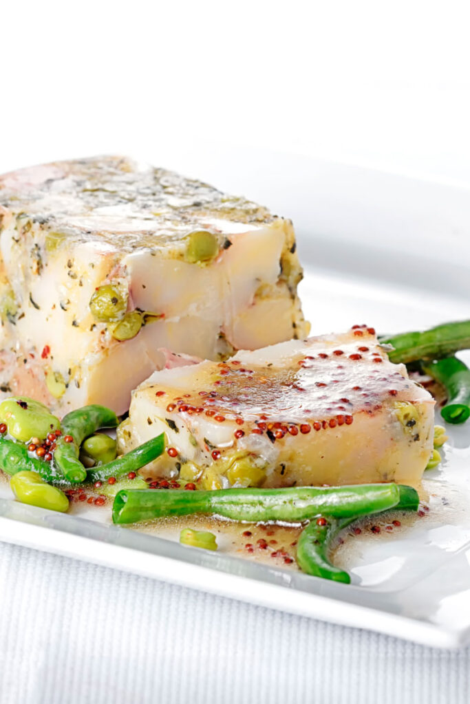 Portrait image of a vegetable terrine featuring peas and potatoes served on a white plate with beans and a mustard dressing