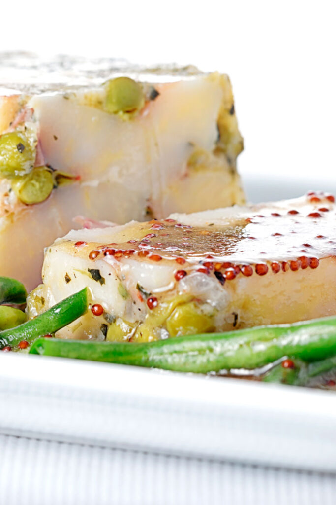 Portrait close up image of a vegetable terrine featuring peas and potatoes served on a white plate with beans and a mustard dressing