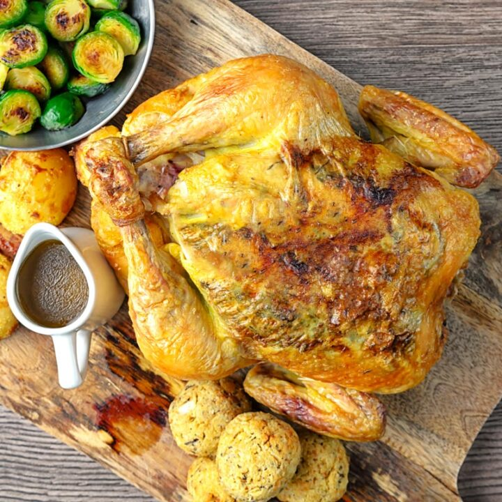 Square overhead image of a perfectly roast whole chicken, roast potatoes, seared Brussels sprouts, sage and onion stuffing balls and a jug of pan gravy