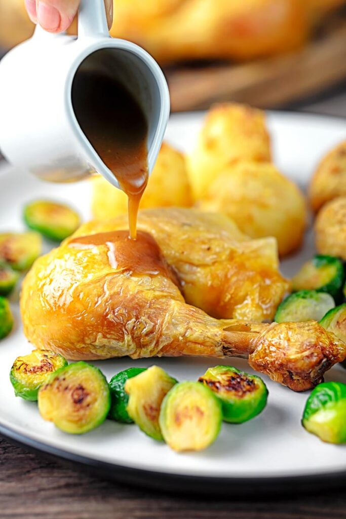 A perfect silky pan gravy being poured of over a roast chicken leg served with Brussels sprouts and roast potatoes