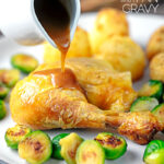 A perfect silky pan gravy being poured of over a roast chicken leg served with Brussels sprouts and roast potatoes with text overlay