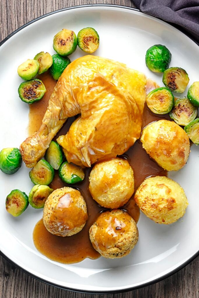 Portrait overhead image of the perfect roast chicken Sunday Lunch featuring a chicken leg, sage and onion stuffing balls, roast potatoes, sprouts and a pan gravy