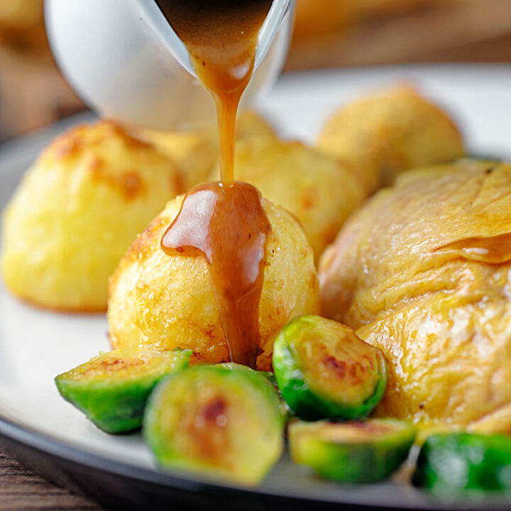 Square image of a perfectly silky gravy being poured over roast potatoes