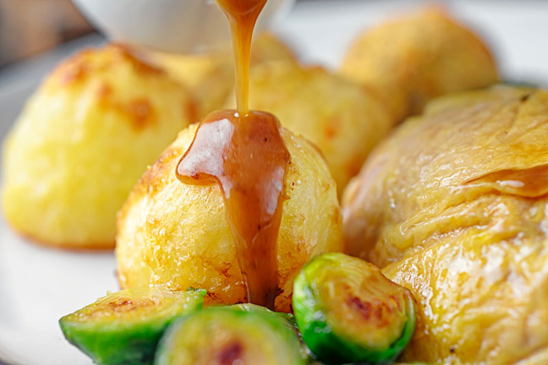 Landscape image of a perfectly silky gravy being poured over roast potatoes