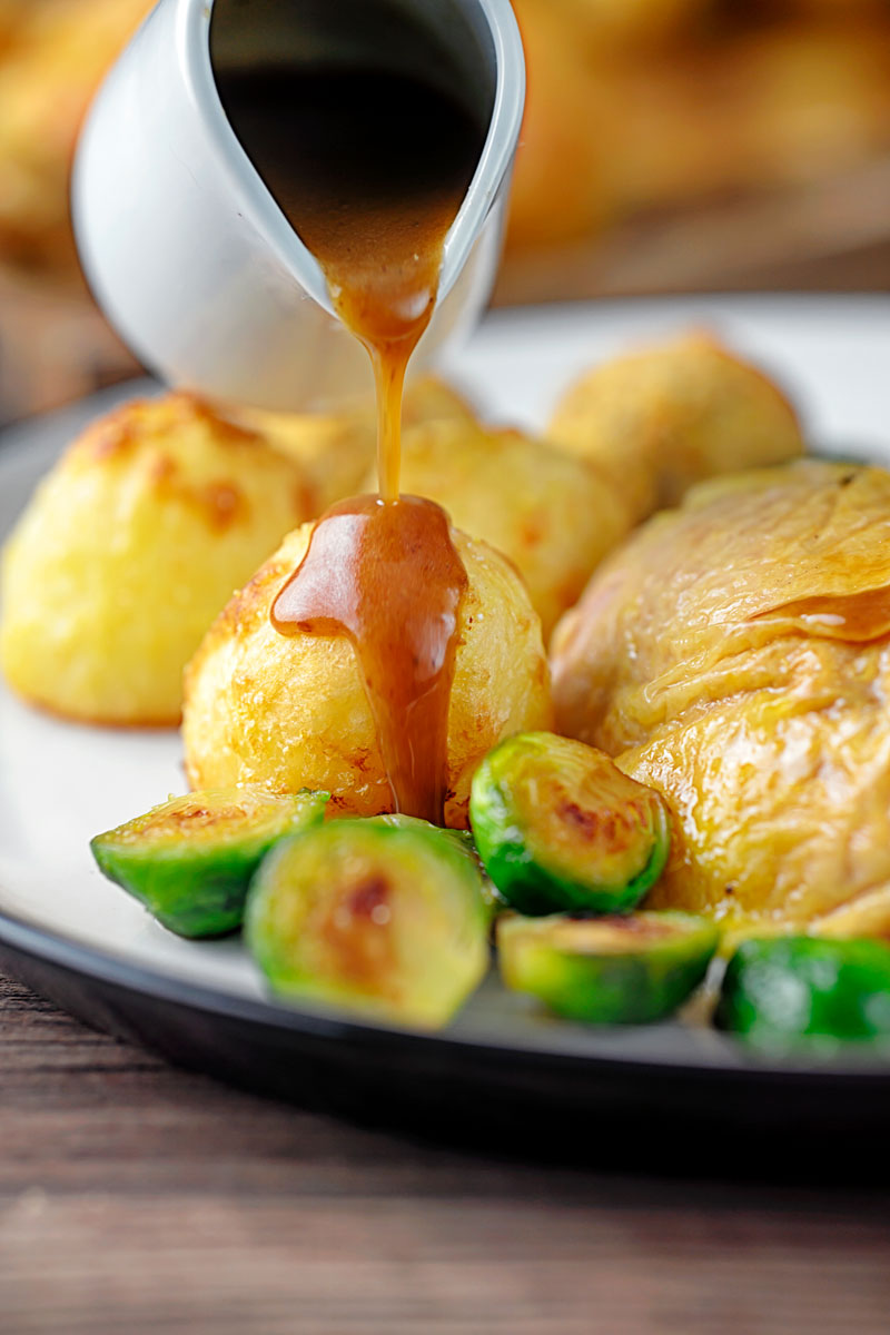 Portrait image of a perfectly silky gravy being poured over roast potatoes