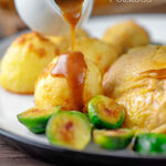 Portrait image of a perfectly silky gravy being poured over roast potatoes with text overlay