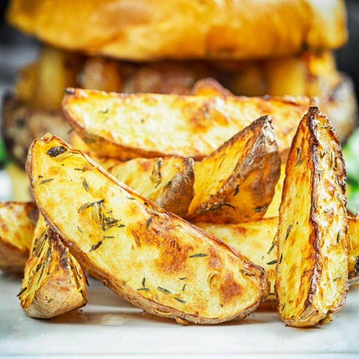 Square close up image of potato wedges served on a white plate